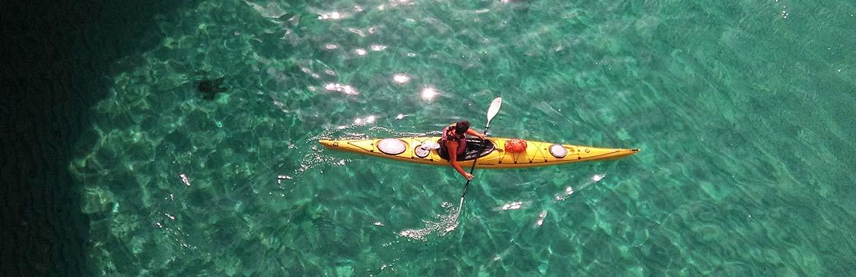 Aerial view of kayaker in crystal blue waters around Menorca